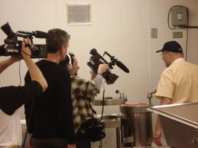 Anthony Bourdain and TV crew watch Sausage Shoppe owner Norm Heinle during production